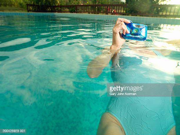Woman taking picture underwater, surface view, close-up
