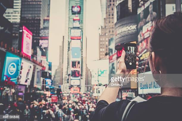 Femme prenant photo avec téléphone portable au Times Squares, à New York