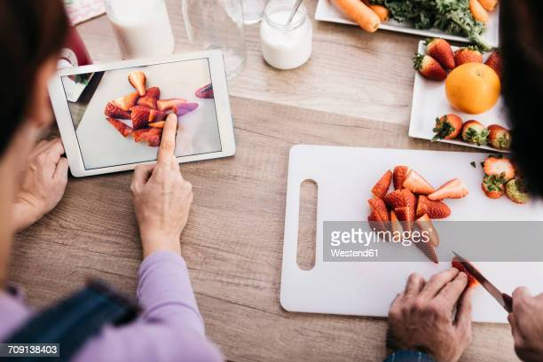 Woman taking picture with tablet while her friend chopping strawberries, partial view