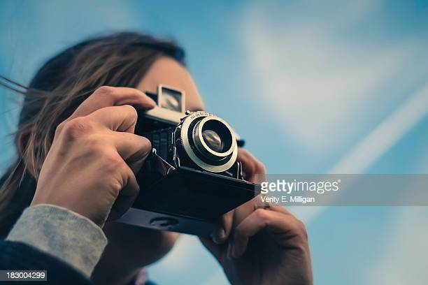 Woman taking picture with vintage 35mm camera
