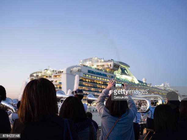 Woman taking picture, Yokohama Scouts sending off the Diamond Princess at the Port of Yokohama.