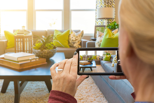 Woman Taking Pictures of A Living Room in Model Home with Her Smart Phone 1159220737