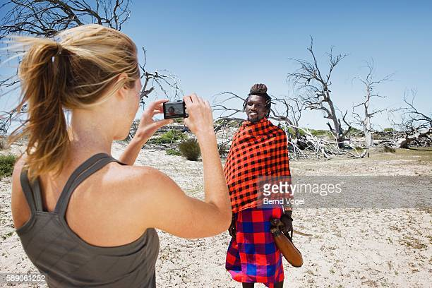 Woman Taking Pictures of a Traditionally Dressed Maasai Man