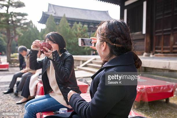 Woman taking pictures of friend easing red bean soup