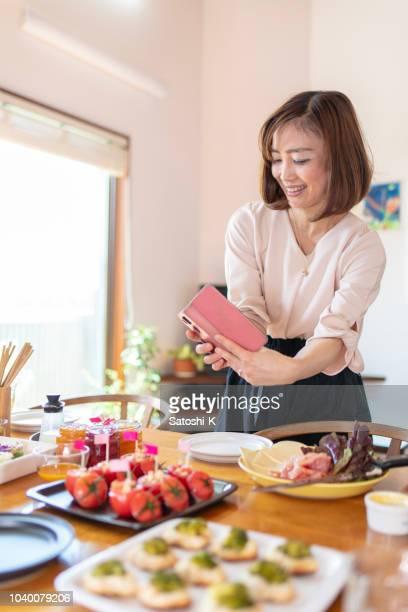 ホーム パーティーで自家製食品の写真を撮る女性 - 人がつくり出したもの ストックフォトと画像