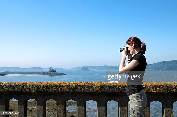 Woman taking pictures of  landscape.