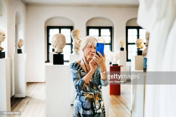 woman taking pictures of museum exhibits - fringe dress stock pictures, royalty-free photos & images