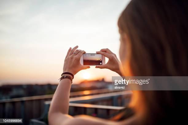 frau, die die bilder des sonnenuntergangs vom dach - horizontal fotos stock-fotos und bilder