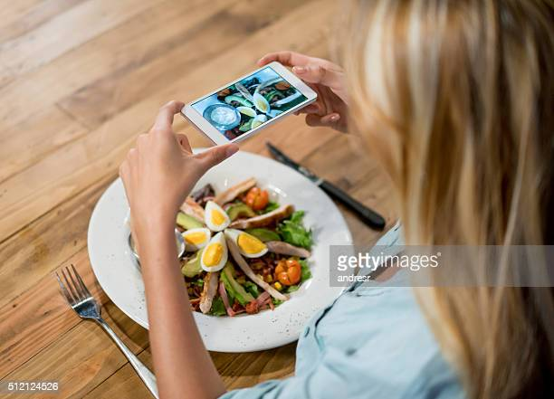 Woman taking pictures of the food
