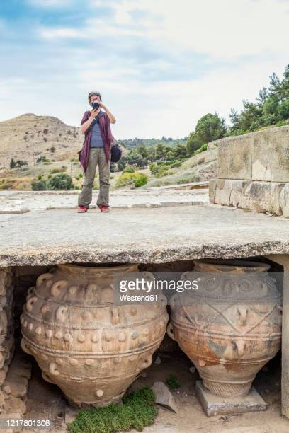 woman taking pictures on site of minoic palace at phaistos, crete, greece - archaeology stock pictures, royalty-free photos & images