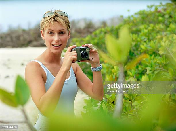 woman taking pictures on the beach - puerto ayora stock pictures, royalty-free photos & images