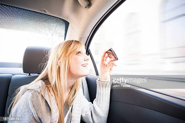 Woman taking pictures out car window