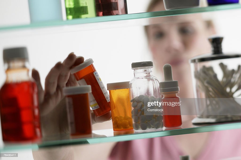 Woman taking pills from medicine cabinet : Stock Photo