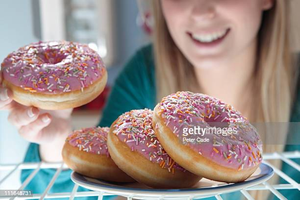 woman taking pink doughnut out of fridge - snack stock pictures, royalty-free photos & images