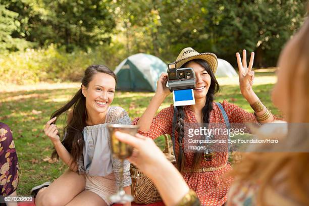 woman taking polaroid photograph at picnic - photography stock pictures, royalty-free photos & images