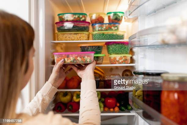 woman taking raw food from refrigerator - storage compartment stock pictures, royalty-free photos & images