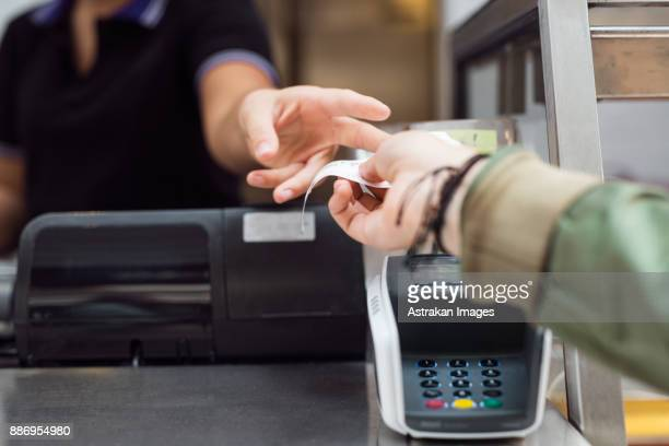 woman taking receipt at checkout counter - receipt stock pictures, royalty-free photos & images