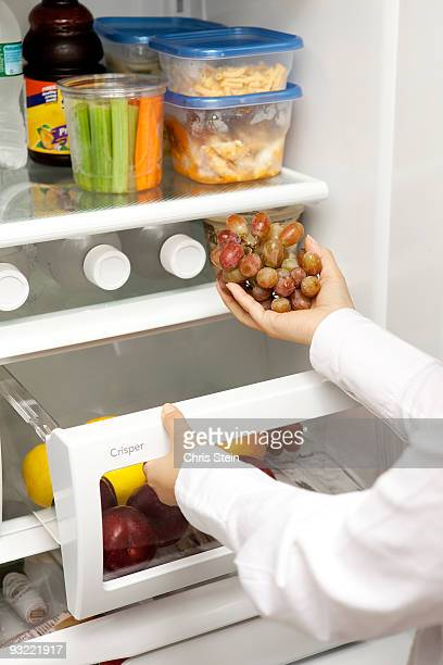 Woman taking red grapes out of a refrgerator