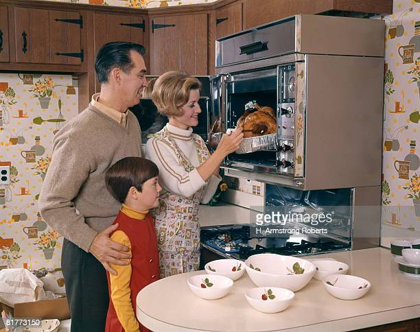 woman taking roast turkey out of wall oven with husband and daughter watching family man girl food holiday. - 1960~1969年 ストックフォトと画像