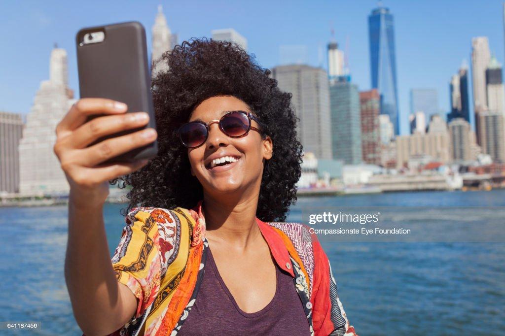 Woman taking self portrait with Manhattan skyline : Stock Photo