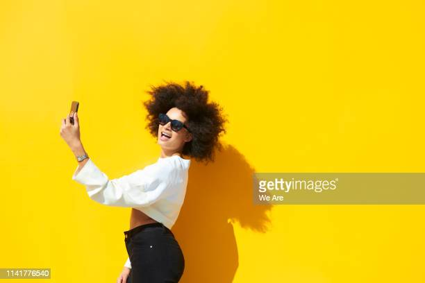 woman taking selfie against yellow background - insouciance photos et images de collection