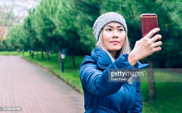 woman taking selfie by mobile phone's camera in public park - blue coat stock pictures, royalty-free photos & images