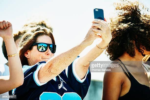Woman taking selfie during game in stadium
