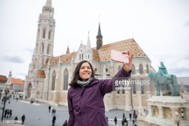 woman taking selfie in budapest - third place stock pictures, royalty-free photos & images