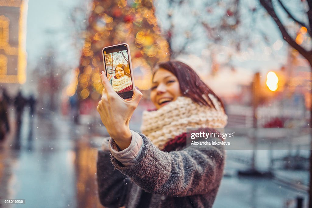 Woman taking selfie in front of the christmas tree : Stock Photo