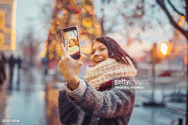 woman taking selfie in front of the christmas tree - filtro de pós produção automática - fotografias e filmes do acervo