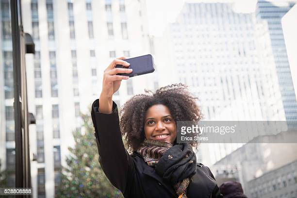 Woman taking selfie in street