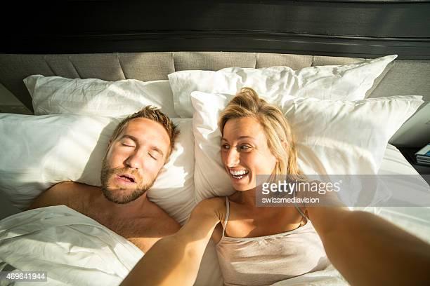 Woman taking selfie, making fun of man sleeping