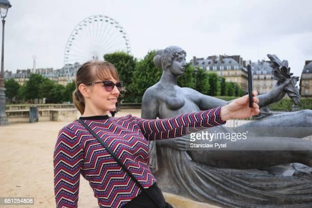Woman taking selfie near Louvre