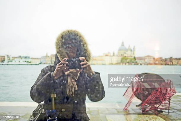 Woman taking selfie of her mirror reflection. Venice stormy weather.
