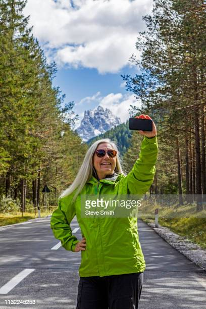 woman taking selfie on highway by tre cime di lavaredo, italy - green coat stock pictures, royalty-free photos & images