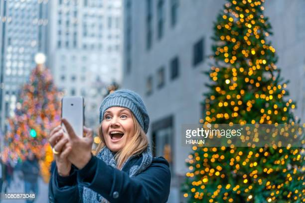 woman taking selfie on smart phone in christmas - new york city christmas stock photos and pictures
