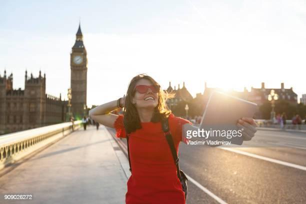 Woman taking selfie on street at sunset