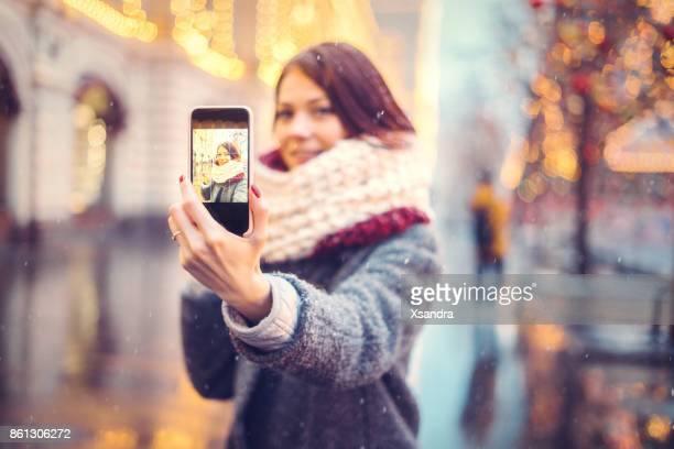 Woman taking selfie on the street decorated for Christmas