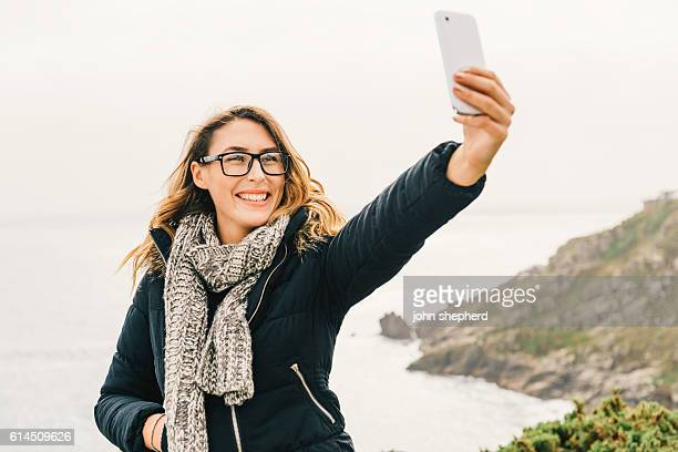 Woman taking Selfie over Cornish Coastline