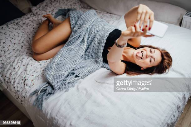 woman taking selfie through mobile phone while lying on bed - fotografische thema's stockfoto's en -beelden
