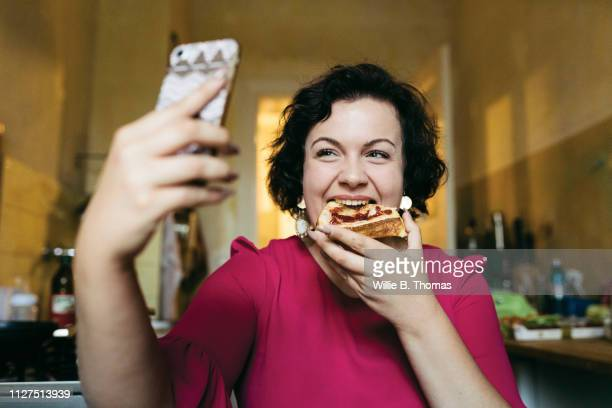 woman taking selfie while eating breakfast - photo messaging stock pictures, royalty-free photos & images
