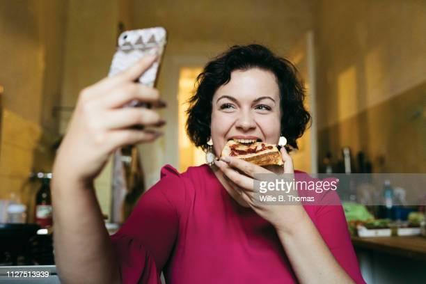 woman taking selfie while eating breakfast - zugänglichkeit stock-fotos und bilder
