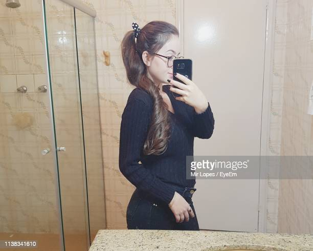 woman taking selfie while standing against mirror - mirror selfie stock pictures, royalty-free photos & images