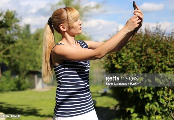 Woman Taking Selfie While Standing Against Sky