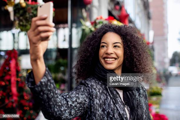 Woman taking selfie while standing on city street
