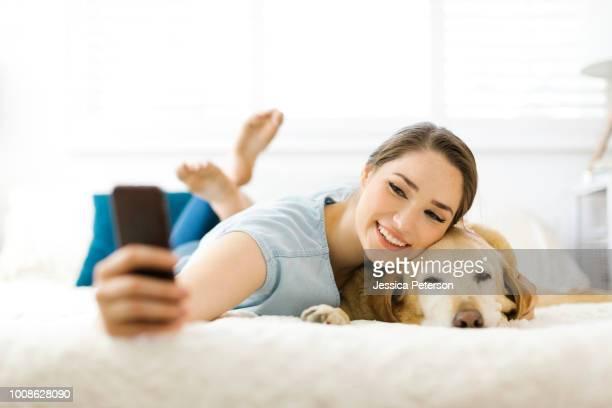 woman taking selfie with dog - op de buik liggen stockfoto's en -beelden