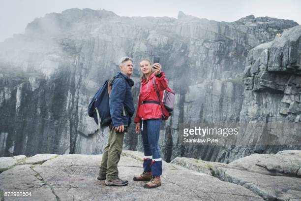 Woman taking selfie with father in mountains