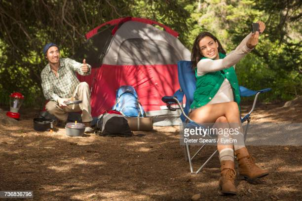 Woman Taking Selfie With Man Gesturing In Background While Camping