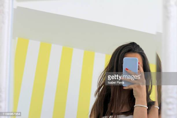woman taking selfie with smartphone in front of mirror - mirror selfie stock pictures, royalty-free photos & images
