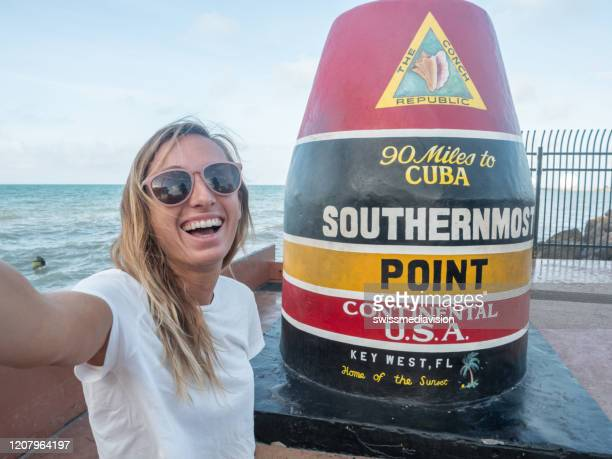woman taking selfie with southernmost point in key west usa - key west stock pictures, royalty-free photos & images
